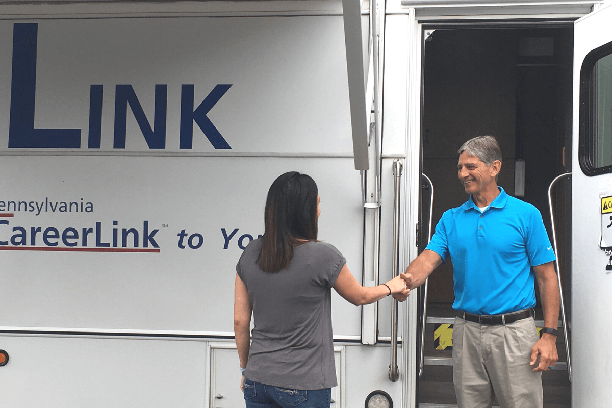 two adults shaking hands outside The Link mobile center