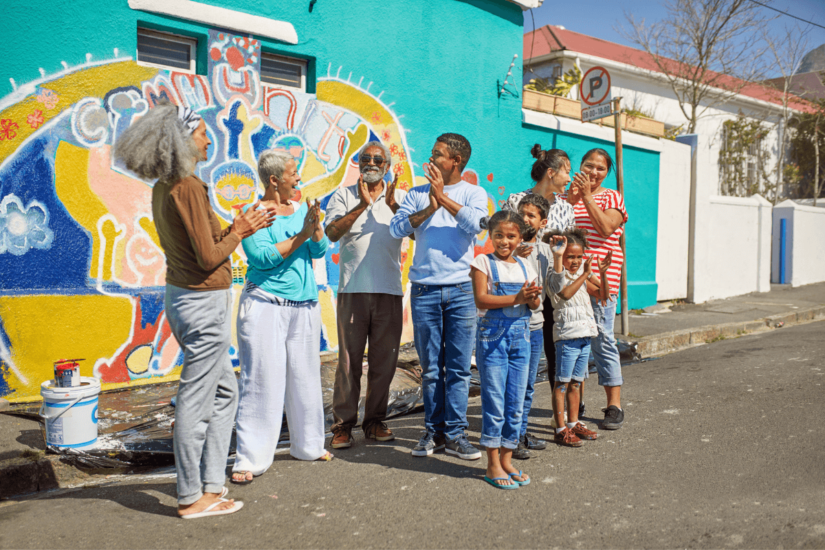diverse group of people standing outside next to a wall mural