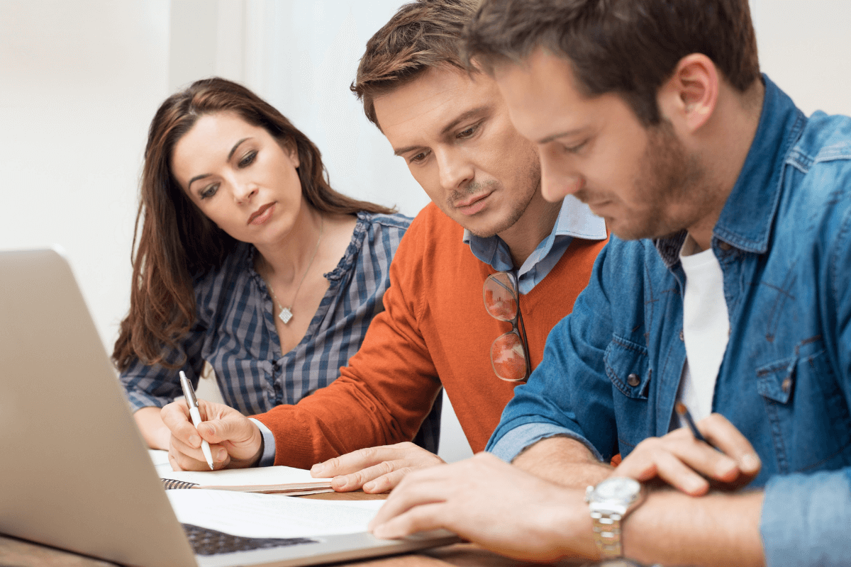 close up of two men and a woman working at a laptop