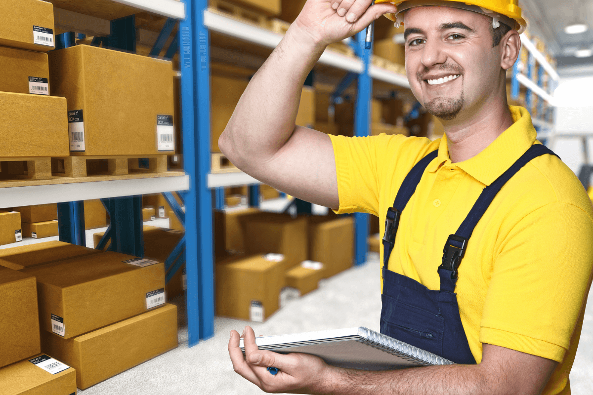 smiling male warehouse worker in a bright yellow shirt