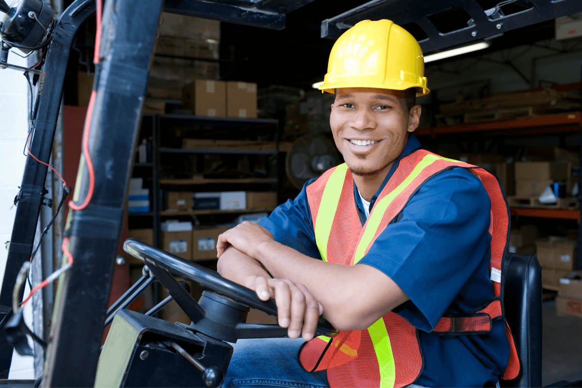 young man in a hard hat and vest sitting on a forklift