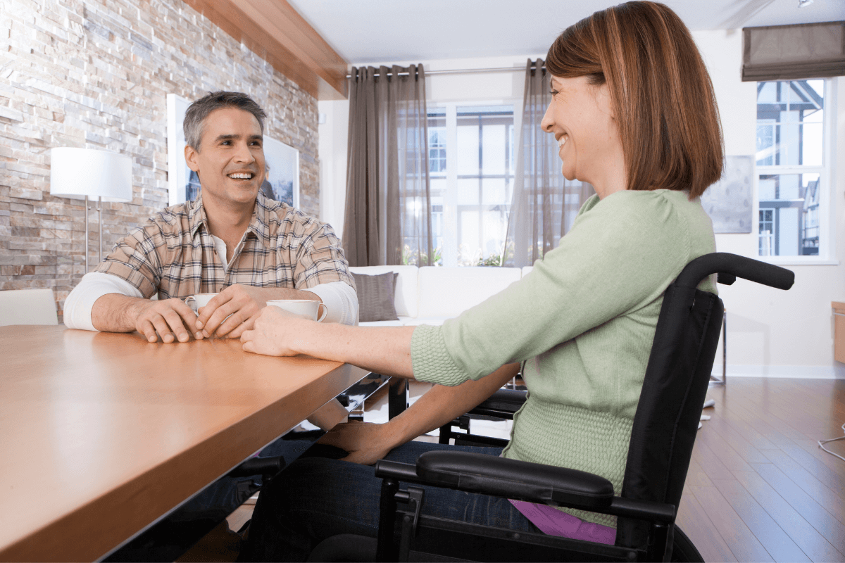 young woman in a wheelchair talking to a man sitting at a desk