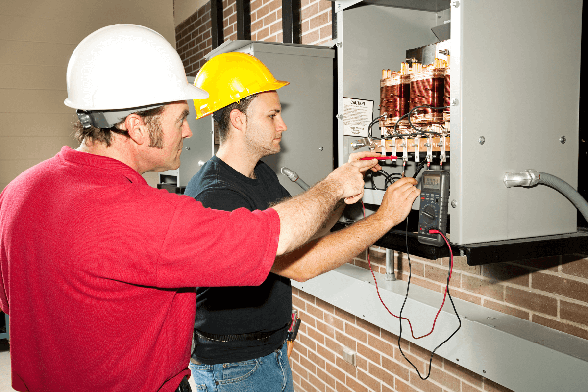 two male workers looking at a electric utility box