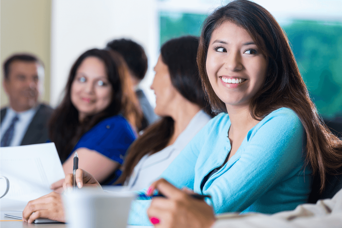 close up of smiling female employees sitting at a table